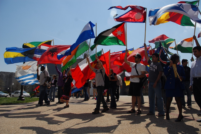 Students carrying flags from various countries