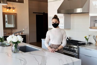 Taylor Olson stands in a kitchen wearing a mask.